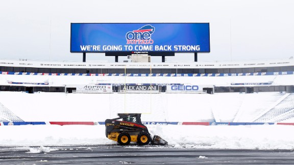 "Workers clear snow from the field at Ralph Wilson Stadium on Sunday, November 23 in Orchard Park, New York. Snowed out at the stadium, the Bills are in Detroit to play their ""home"" NFL football game against the New York Jets on Monday night. Western New York continues to dig out from a lake-effect storm that dumped about a year"