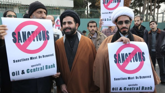 Iranian men hold placards during a demonstration outside the Tehran Research Reactor in the capital Tehran on November 23, 2014, to show their support to Iran's nuclear programme. Iran and six world powers are holding talks in Vienna to reach a lasting agreement on Tehran's disputed nuclear programme before November 24. Such a deal, after 12 years of rising tensions, is aimed at easing fears that Tehran will develop nuclear weapons under the guise of its civilian activities -- an ambition the Islamic republic has always fiercly denied. AFP PHOTO/ATTA KENAREATTA KENARE/AFP/Getty Images