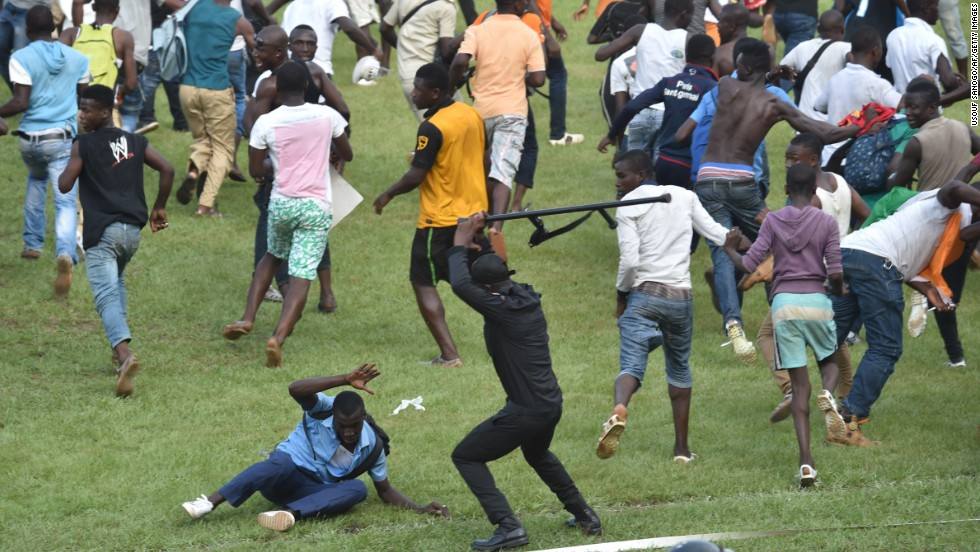 A police officer beats a man in Abidjan, Ivory Coast, as people run on the field following a soccer match between Ivory Coast and Cameroon on Wednesday, November 19. The 0-0 draw clinched a place for both countries in next year's Africa Cup of Nations.