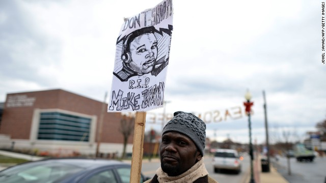 A protester displays a placard depicting 18-year-old Michael Brown outside the police station in Ferguson, Missouri on November 24, 2014. A US grand jury has reached a decision on whether or not to indict a white police officer for shooting dead an unarmed black teenager in a tense suburb, prosecutors said on November 24. There is no indication yet as to whether or not officer Darren Wilson will face charges for the death of Michael Brown on August 9, 2014 in the community of Ferguson, just outside St Louis. AFP PHOTO/Jewel Samad (Photo credit should read JEWEL SAMAD/AFP/Getty Images)