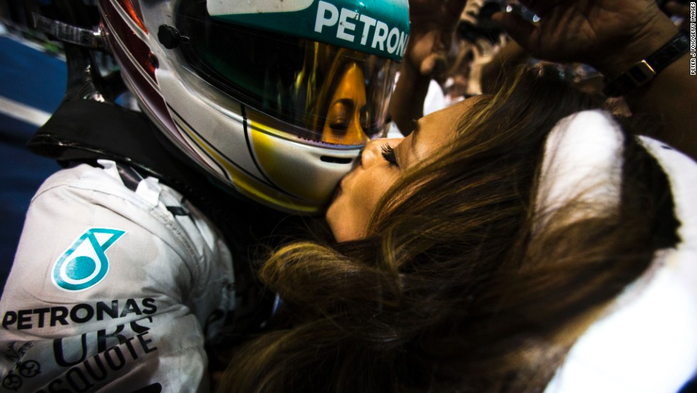 Singer Nicole Scherzinger kisses her boyfriend, Formula One driver Lewis Hamilton, after he clinched the championship Sunday, November 23, in Abu Dhabi, United Arab Emirates. The British driver has now won two F1 titles.