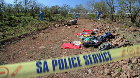 A forensics team searches the area around the body of a poached rhino looking for clues. The rhino was shot along Kruger National Park's border with Mozambique. The investigators have had such a backlog of rhino poaching cases that it has taken them 10 days to get to this one.