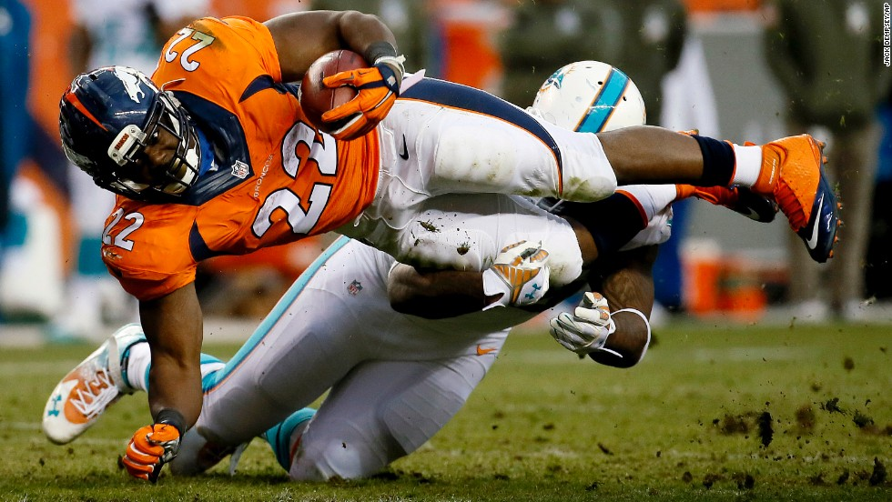 Denver Broncos running back C.J. Anderson is hit by Miami's Randy Starks during the Broncos' 39-36 home victory on Sunday, November 23.