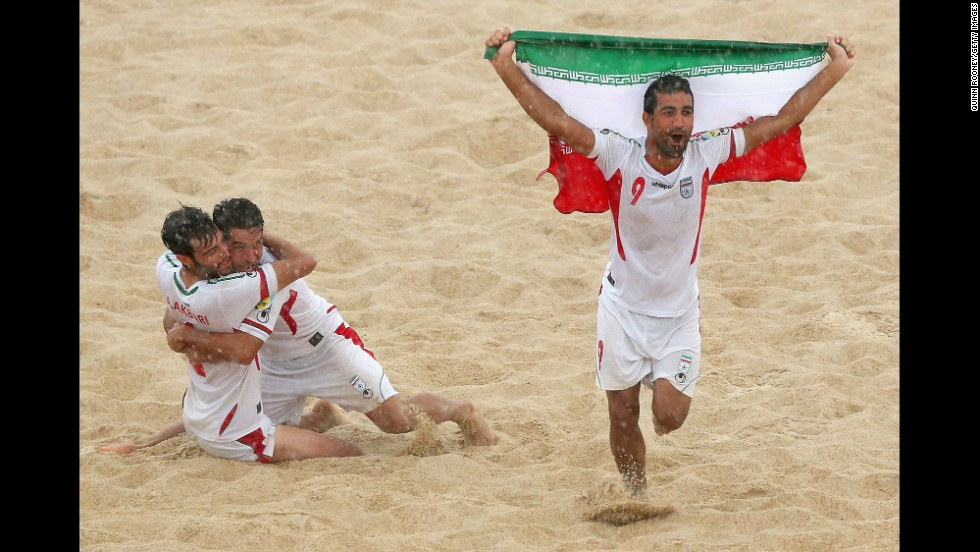 Mohammadali Mokhari, right, and some of his Iranian beach soccer teammates celebrate Friday, November 21, after they defeated Japan to win the gold medal at the Asian Beach Games in Phuket, Thailand.