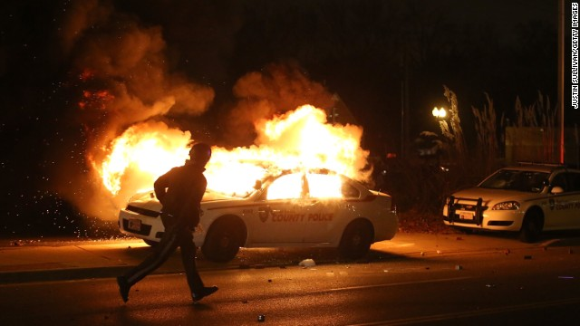 A police officer runs by a burning police car in Ferguson, Missouri, on Monday, November 24.