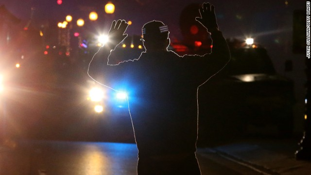 A protestor stands in front of police vehicles with his hands up in Ferguson.