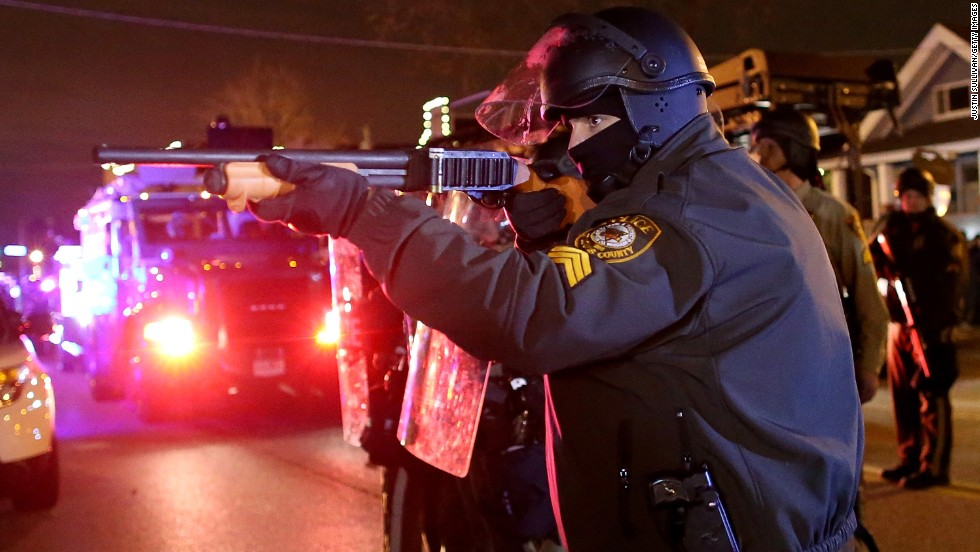 A police officer points his rifle at