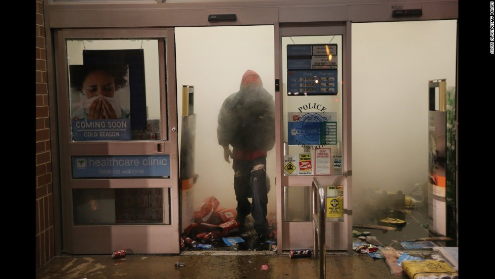 A looter in Ferguson walks out of a burning Walgreens on November 24.