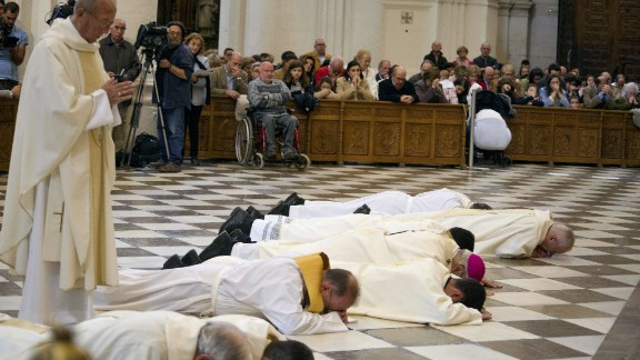Granada's Archbishop, Francisco Javier Martinez (purple skullcap) prostrates in front of cathedral's high altar to ask forgiveness for 'the scandals.'