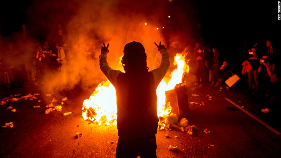 Demonstrators gather around a fire in the streets of Oakland, California, on November 24.