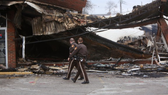 """Police officers walk past the smoldering remains of a beauty supply store in Ferguson, Missouri, on Tuesday, November 25. Ferguson has been struggling to return to normal since Michael Brown, an unarmed black teenager, was killed by Darren Wilson, a white police officer, on August 9. The grand jury did not indict Wilson in the case, prompting new waves of protests in Ferguson and <a href=""""http://www.cnn.com/2014/11/25/justice/gallery/national-ferguson-protests/index.html"""">across the country.</a>"""