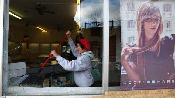 A woman cleans up glass from a business