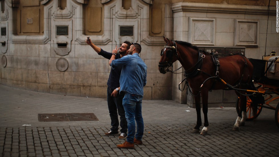 Men take a selfie with a horse in the downtown area of Seville, Spain, on Friday, November 21.