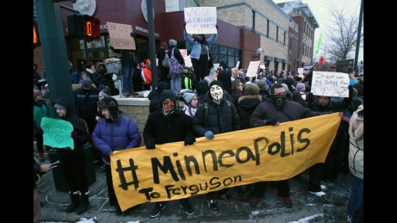 Demonstrators gather November 25 outside the Minneapolis Police Department's Third Precinct to protest Monday's announcement.
