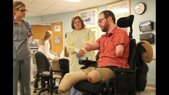 """Will Lautzenheiser, a former professor of film production and screenwriting, lost his limbs in 2011 after a battle with a severe streptococcal infection. But he received two arm transplants in Boston. """"To have come here and to have received this gift is really astonishing to me."""" Here, Lautzenheiser meets with members of the plastic surgery transplant clinical care team in June 2014 at Brigham and Women's Hospital. Click through to see his remarkable medical journey:"""