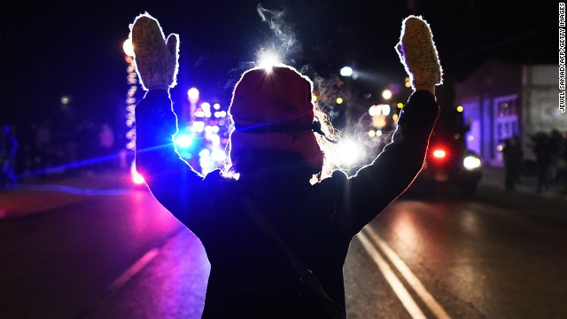 A protester holds her hands up in front of police in Ferguson, Missouri, on Tuesday, November 25.