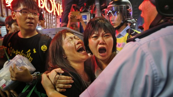 Protesters cry as police officers try to stop them from blocking the road in the Mong Kok district of Hong Kong on Wednesday, November 26.