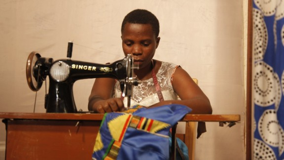 Mama Ngawerie helps Mbabazi tailor clothes to customers