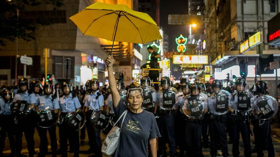 A pro-democracy activist holds a yellow umbrella in front of a police line on November 25, 2014 in Hong Kong.