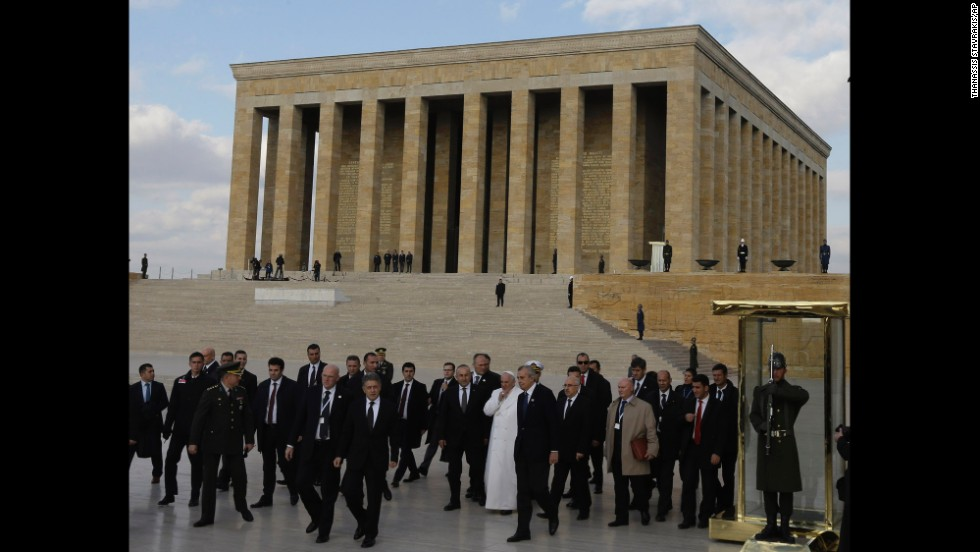 The Pope, surrounded by security and officials, walks the grounds of the mausoleum November 28.
