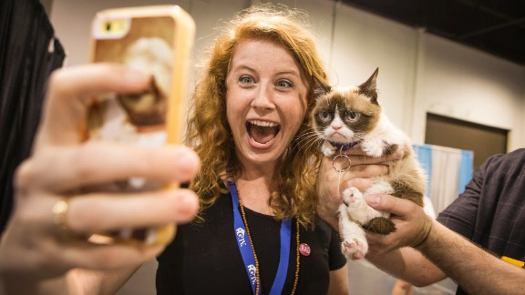 """A fan takes a selfie with <a href=""""http://money.cnn.com/2013/09/18/news/companies/grumpy-cat-friskies/"""">""""Grumpy Cat,""""</a> the Internet celebrity famous for her perpetual scowl, on Friday, June 27, at the Anaheim Convention Center in Anaheim, California. The cat, whose real name is Tardar Sauce, is the official """"spokescat"""" for Friskies cat food and <a href=""""https://www.thefriskies.com"""" target=""""_blank"""" target=""""_blank"""">its award show</a> for the best original cat videos."""