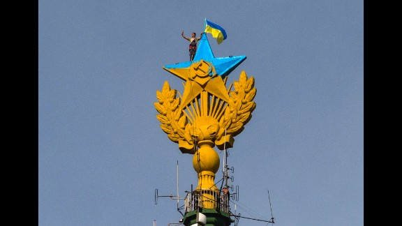 A worker takes a selfie before removing a Ukrainian flag that was attached by protesters atop a Stalin-era skyscraper in Moscow on Wednesday, August 20. Protesters scaled the skyscraper and painted the Soviet star in the national colors of Ukraine. The dangerous prank, which set Russian social networking sites abuzz, drew a harsh response from the police.