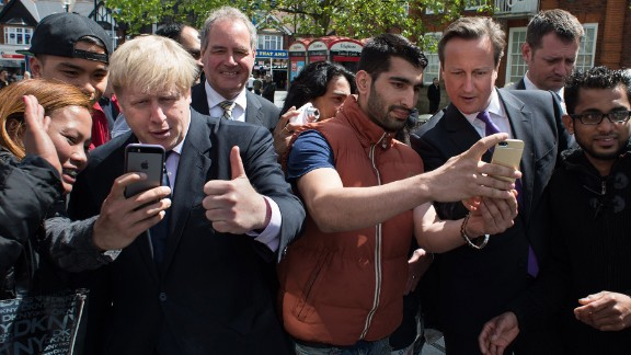 """London Mayor Boris Johnson, third from left, and British Prime Minister David Cameron, third from right, take selfies with locals as they campaign in London on Monday, May 12. Cameron told the London Evening Standard that the selfie craze these days makes campaigning take longer. """"You can be walking down the street for a chat, but until you"""