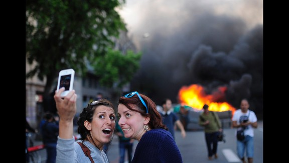 Tourists take a selfie as demonstrators burn a trash container during a May Day rally in Barcelona, Spain, on Thursday, May 1. May Day is also known as International Workers