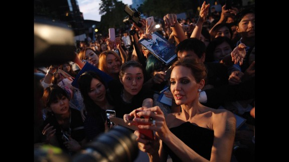 """Actress Angelina Jolie tries to take pictures with fans as she attends the Tokyo premiere of her movie """"Maleficent"""" on Monday, June 23. See the life of Angelina Jolie"""