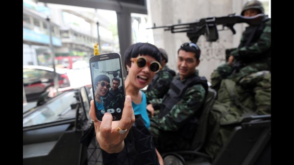 A woman takes a selfie in front of army soldiers standing guard in Bangkok, Thailand, on Tuesday, May 20. A couple of days later, Thailand