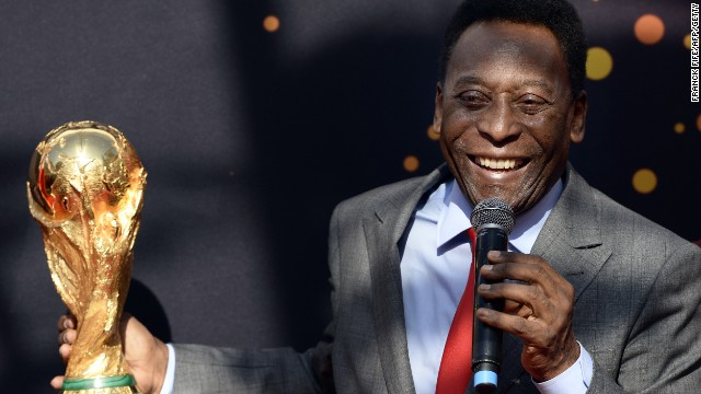 Brazilian football legend Pele looks at the FIFA World Cup trophy during the FIFA World Cup Trophy event on March 9, 2014.