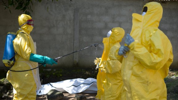 Guinean Red Cross workers prepare to carry the corpse of a victim of Ebola in Macenta on November 21, 2014. The World Health Organisation said that 5,420 people have so far died of Ebola across eight countries, out of a total 15,145 cases of infection, since late December 2013.