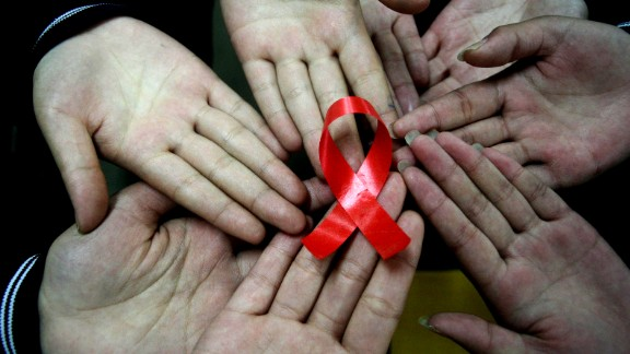 File photo: Chinese students show a handmade red ribbon one day ahead of the the World AIDS Day, at a school in Hanshan, east China