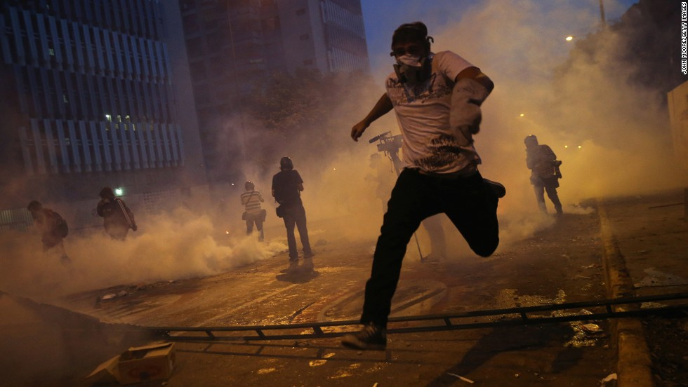 "<strong>February 27:</strong> Protesters run from tear gas fired by the Venezuelan National Guard during an anti-government demonstration in Caracas, Venezuela. For months, protesters unhappy with Venezuela's economy and rising crime <a href=""http://www.cnn.com/2014/02/18/world/gallery/venezuela-protests/index.html"">clashed with security forces.</a>"