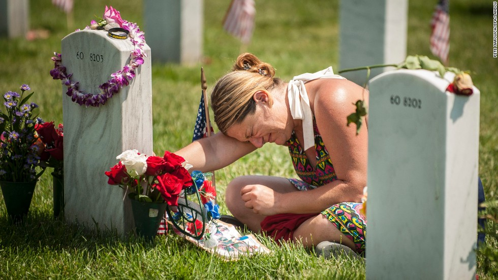 <strong>May 26:</strong> Laura Youngblood weeps over the grave of her husband, Travis L. Youngblood, at Arlington National Cemetery in Arlington, Virginia. It was Memorial Day in the United States.
