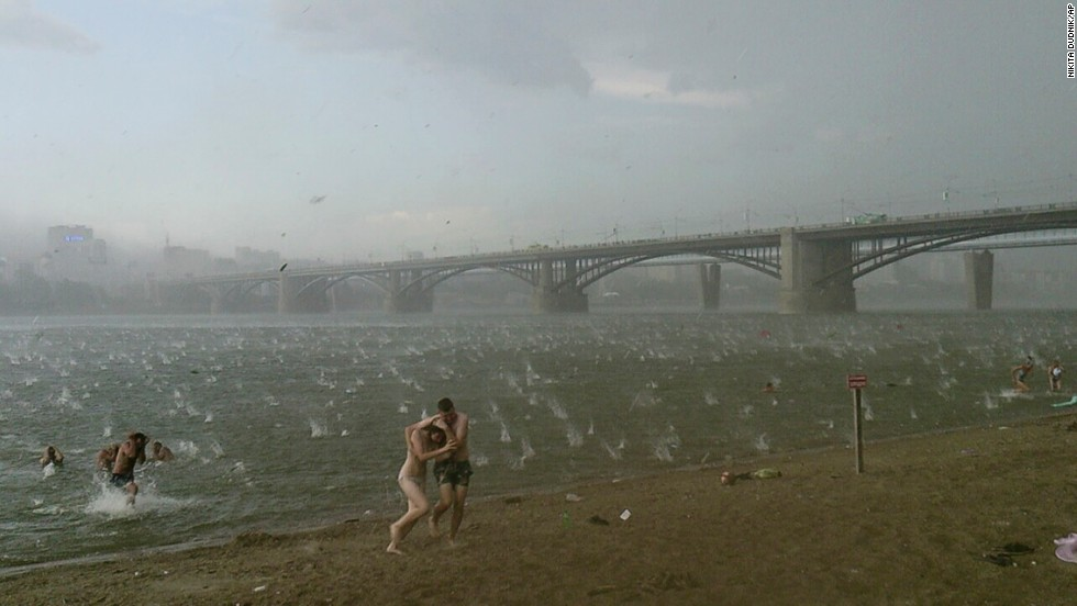 <strong>July 12:</strong> People run for shelter during a hailstorm at the Ob River in Novosibirsk, Russia.