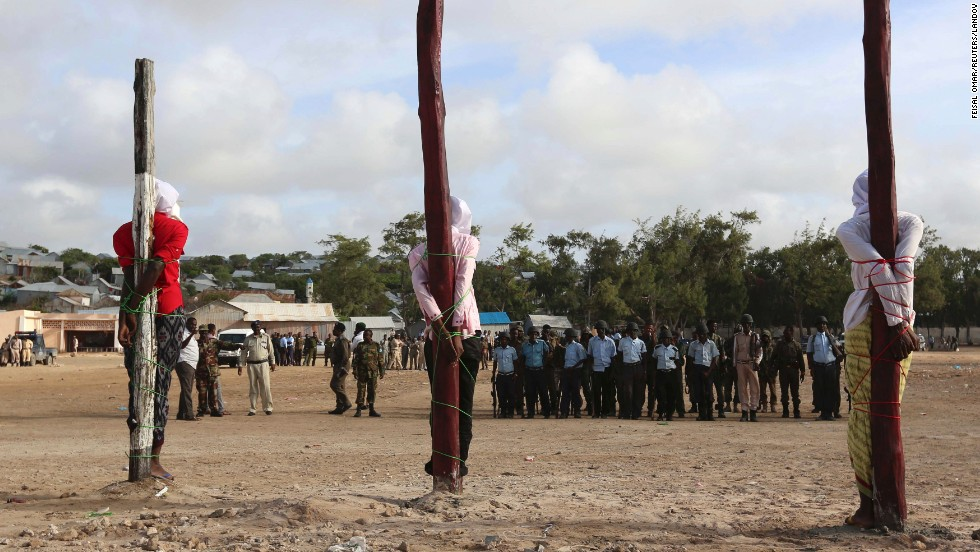 <strong>August 3:</strong> Three men found guilty by a Somali military court of killing civilians and masterminding an attack on the presidential palace are tied to poles shortly before they were executed by a firing squad in Mogadishu, Somalia. The three were members of the militant group Al-Shabaab.