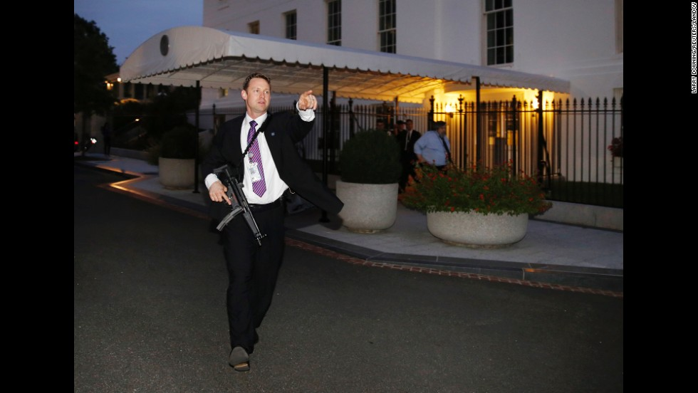 "<strong>September 19:</strong> A U.S. Secret Service agent hurries people to evacuate the White House complex moments after a security breach. President Barack Obama and his family were not at home when an intruder scaled the fence and entered the White House, but a congressional inquiry uncovered other security lapses this year and <a href=""http://www.cnn.com/2014/10/01/politics/gallery/obama-administration-resignations-firings/index.html"">led to the resignation</a> of Secret Service Director Julia Pierson."