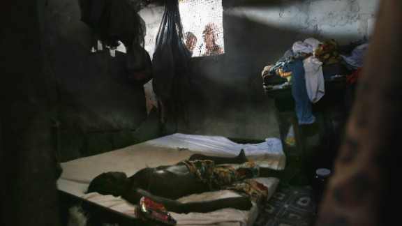People peer into a bedroom in Monrovia as a dead body awaits the arrival of an Ebola burial team in October. Globally, the world