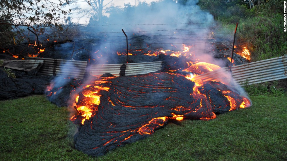 "<strong>October 28:</strong> Lava from <a href=""http://www.cnn.com/2014/10/28/us/gallery/kilauea-volcano/index.html"">the Kilauea volcano</a> pours past a boundary fence in Pahoa, Hawaii. The flow was picking up speed, prompting emergency officials to close part of the main road through town and tell residents to be prepared to evacuate."