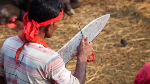 A knifeman sharpens his blade at Nepal's Gadhimai festival.