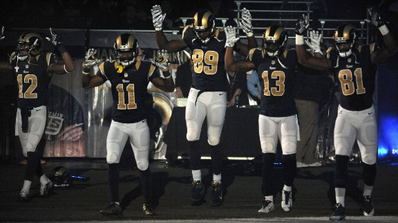 Members of the St. Louis Rams raise their arms as they walk onto the football field in St. Louis before their game against the Oakland Raiders on November 30.