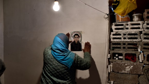 A Syrian Kurdish refugee pins a picture of her son on a wall in Suruc on Tuesday, November 11. She says he died during a battle in Kobani.