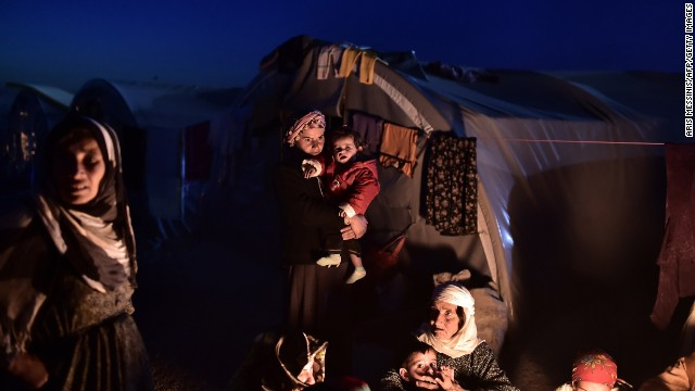 Syrian Kurdish refugees sit outside tents at a refugee camp in Suruc on November 11.