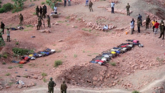 Soldiers of Kenyan Defence Forces look over the bodies of some  36 Kenyans  as they lie at a quarry, Tuesday, Dec. 2, 2014. Kenya police say that at least 36 quarry workers were killed in an attack in northern Kenya  by suspected Islamic extremists from Somalia. Kenyan police chief David Kimaiyo confirmed the workers were killed early Tuesday in Mandera County. (AP Photo) ,