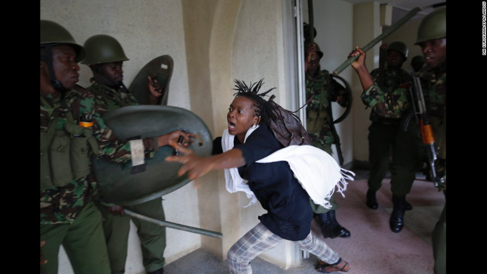 <strong>May 20:</strong> A woman flees as a riot police officer beats her with a baton in Nairobi, Kenya. Hundreds of Nairobi University students took to the streets and faced riot police as they protested against a proposed increase in school fees.