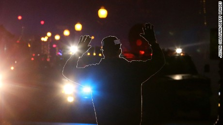 A protestor stands in front of police vehicles with his hands up during a demonstration in Ferguson, Missouri.