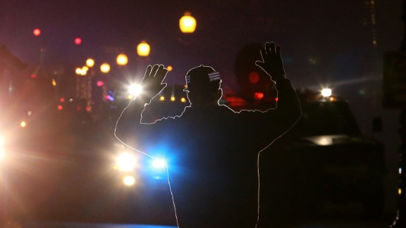 """A protester in Ferguson, Missouri, stands in front of police vehicles with his hands up on November 24, 2014. A grand jury's decision not to indict police Officer Darren Wilson in the killing of Michael Brown prompted waves of protests in Ferguson and across the country. The """"hands up, don't shoot"""" gesture became a rallying cry and protest symbol."""
