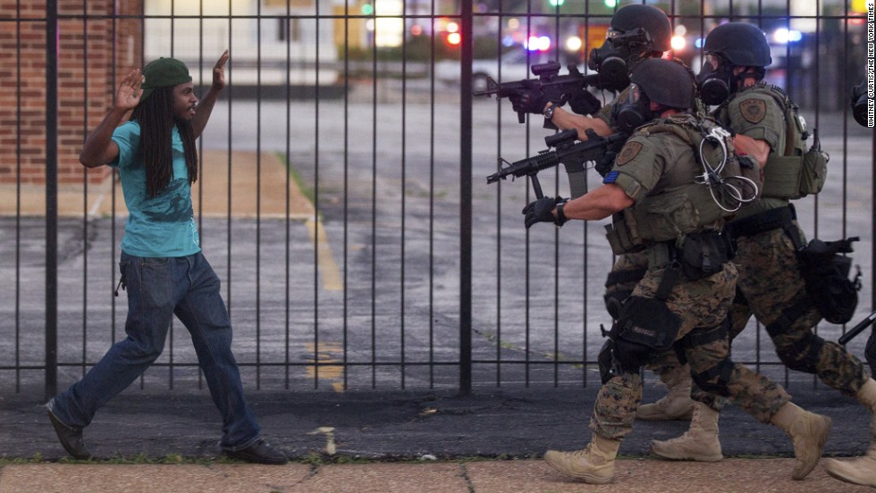 "<strong>August 11:</strong> Police wearing riot gear confront a man during <a href=""http://www.cnn.com/2014/08/14/us/gallery/ferguson-missouri-protests/index.html"">protests in Ferguson, Missouri.</a> Some protests in the city turned into clashes between angry citizens and police after Michael Brown, an unarmed black teenager, was killed by Darren Wilson, a white police officer, on August 9."