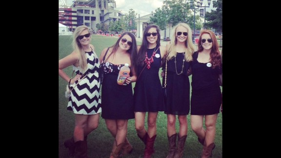 """At the University of South Carolina, Southern gentlemen """"allow our ladies to take the spotlight,"""" says student Byron Thomas, who shot this photo of his friends. Girls typically wear garnet or black sundresses paired with """"cowgirl"""" boots. """"You'll see a lot of girls walking home barefoot because the cowgirl boots hurt their feet from all the standing and jumping,"""" Thomas said."""